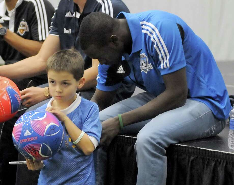 Sandy Hook first grader Ryan Zaniewski, 6, gets his jersey signed by American soccer player, Marcus Tracy, also of Newtown, during the Soccer Night in Newtown on Monday Jan. 7, 2013. Photo: Lisa Weir / The News-Times Freelance