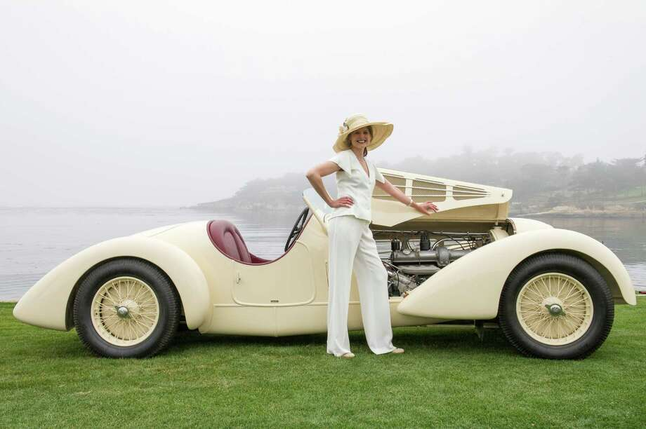 An attendee poses for a photograph in front of a 1934 Alfa 8C2300 Zagato Body during the 2013 Pebble Beach Concours d' Elegance in Pebble Beach, California, U.S., on Sunday, Aug. 18, 2013. The annual event in its 63rd year raised $1.277 million U.S. dollars for charity and showcased 248 cars, 48 from abroad. Photo: David Paul Morris, Bloomberg / 2013 Bloomberg Finance LP
