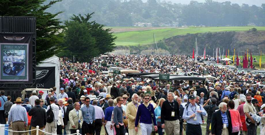 Attendees crowd the 18th fairway of Pebble Beach Golf Links during the 2013 Pebble Beach Concours d' Elegance in Pebble Beach, California, U.S., on Sunday, Aug. 18, 2013. The annual event in its 63rd year raised $1.277 million U.S. dollars for charity and showcased 248 cars, 48 from abroad. Photo: David Paul Morris, Bloomberg / 2013 Bloomberg Finance LP