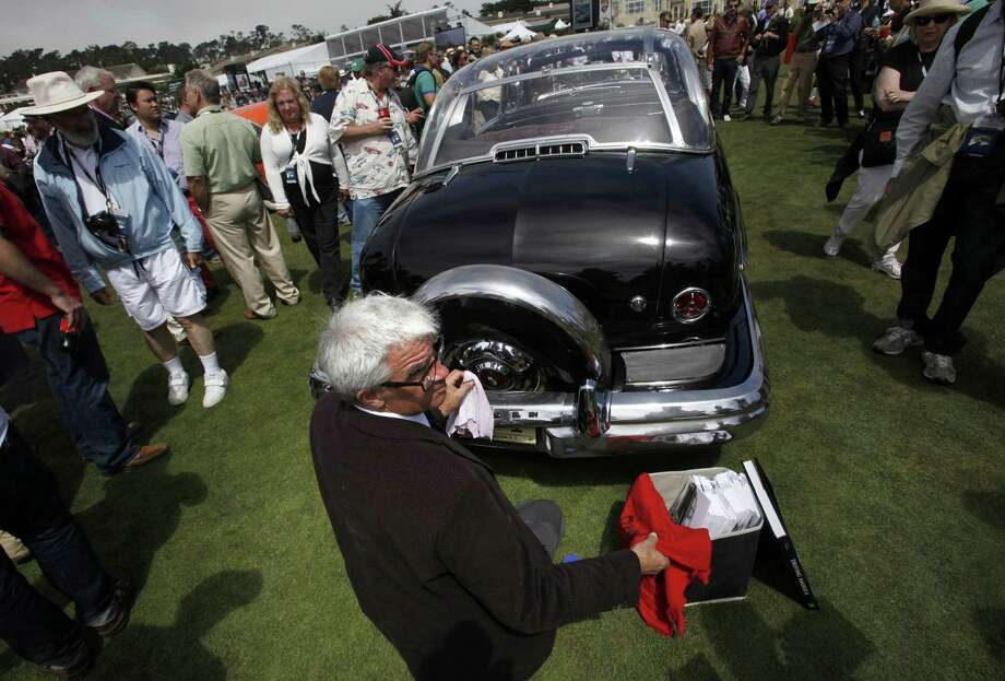 "Robert Coyle works on polishing a 1950 Lincoln Presidential Limousine which served Truman, Eisenhower and Kennedy as nearly 10,000 people enjoy the display of around 200 collector cars on the eighteenth fairway in Pebble Beach, California, at the Pebble Beach Concours d'Elegance, which has grown into the top-ranking collector car show in the world, on August 18, 2013. Automobiles and motorcycles competing for the Concours ""Best of Show"" award are judged for their historical accuracy, their technical merit and their style. Photo: BOB CHAMBERLIN, McClatchy-Tribune News Service / Los Angeles Times"