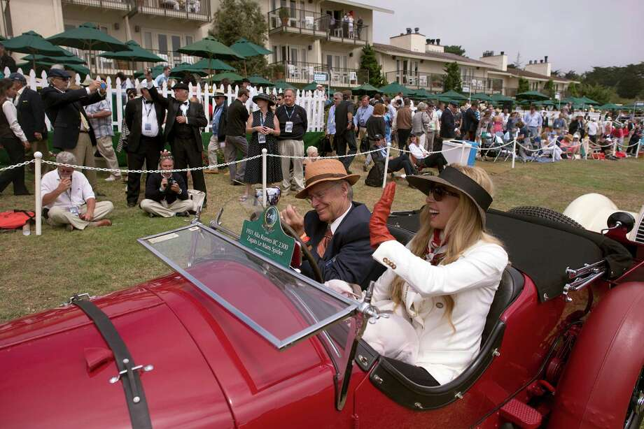 Rob and Melani Walton wave to spectators as they cue up in front of the Concours d'Elegance stage Sunday, August 18th, 2013 in in their 1931 Alfa Romeo 8C 2300 Le Mans Spider. Photo: Matthew Hintz, Associated Press / Monterey County Herald