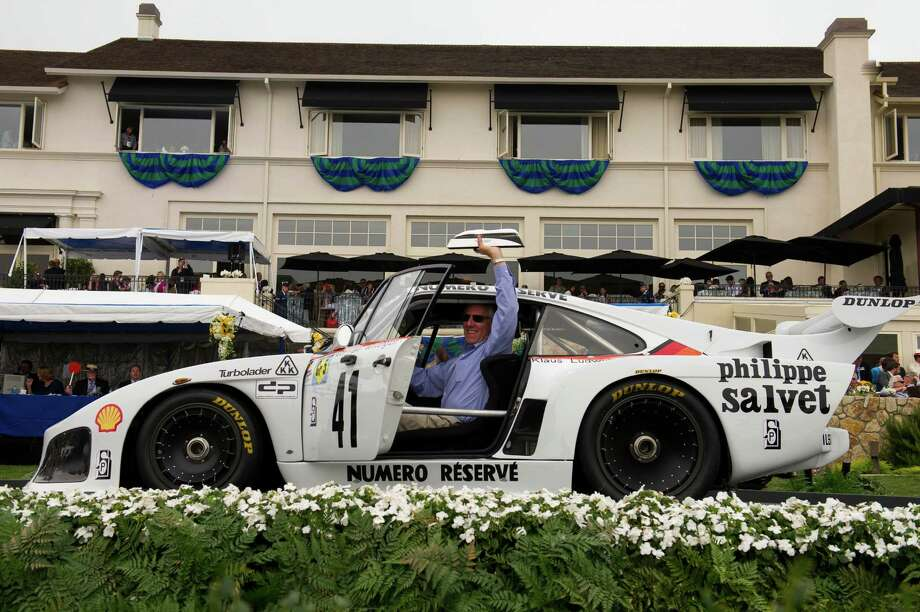 Bruce Meyer holds his trophy as he drives his 1979 Porsche 935 K3 Coupe during the 2013 Pebble Beach Concours d' Elegance in Pebble Beach, California, U.S., on Sunday, Aug. 18, 2013. The annual event in its 63rd year raised $1.277 million U.S. dollars for charity and showcased 248 cars, 48 from abroad. Photo: David Paul Morris, Bloomberg / 2013 Bloomberg Finance LP