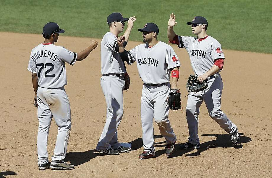 Boston Red Sox players Xander Bogaerts, from left, Stephen Drew, Shane Victorino, and Daniel Nava celebrate after the Red Sox beat the San Francisco Giants in a baseball game in San Francisco, Wednesday, Aug. 21, 2013. (AP Photo/Jeff Chiu) Photo: Jeff Chiu, Associated Press