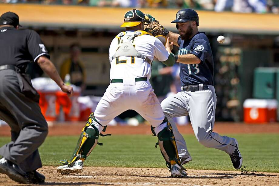 OAKLAND, CA - AUGUST 21: Dustin Ackley #13 of the Seattle Mariners collides with Stephen Vogt #21 of the Oakland Athletics to score a run during the sixth inning at O.co Coliseum on August 21, 2013 in Oakland, California. (Photo by Jason O. Watson/Getty Images) Photo: Jason O. Watson, Getty Images