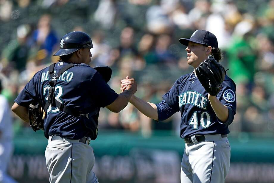 OAKLAND, CA - AUGUST 21: Danny Farquhar #40 of the Seattle Mariners celebrates with Henry Blanco after the game against the Oakland Athletics at O.co Coliseum on August 21, 2013 in Oakland, California. The Seattle Mariners defeated the Oakland Athletics 5-3. (Photo by Jason O. Watson/Getty Images) Photo: Jason O. Watson, Getty Images