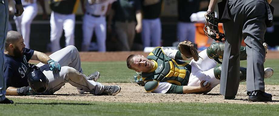 Oakland Athletics catcher Stephen Vogt, right, reacts after Seattle Mariners' Dustin Ackley, left, was called safe at home plate in the sixth inning of a baseball game Wednesday, Aug. 21, 2013, in Oakland, Calif. (AP Photo/Ben Margot) Photo: Ben Margot, Associated Press