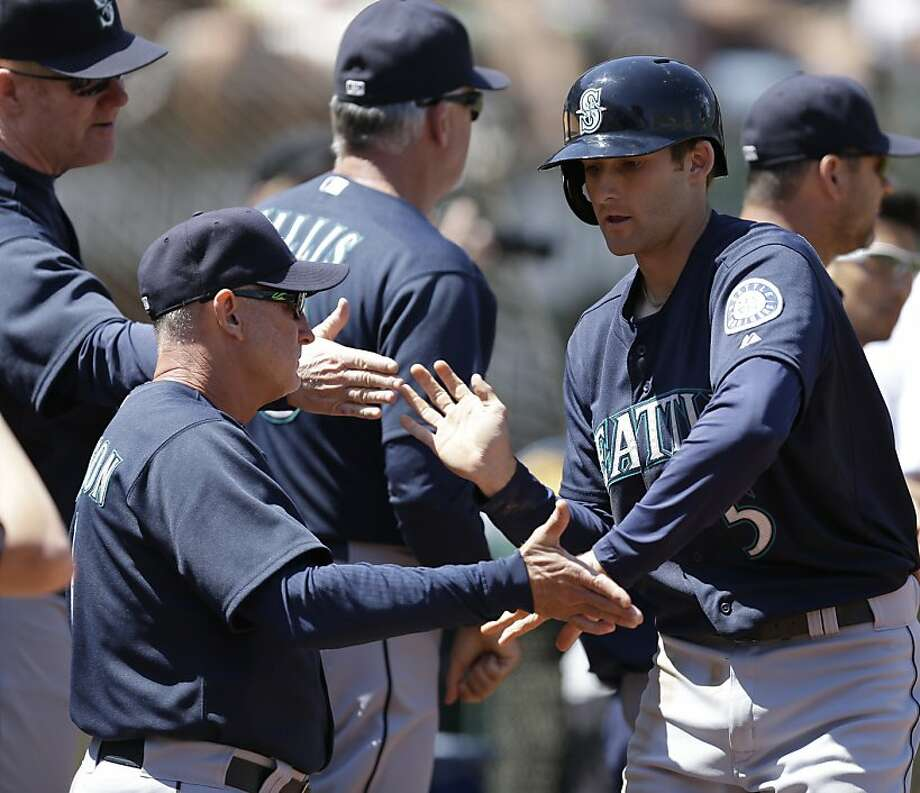 Seattle Mariners' Brad Miller, right, is congratulated after hitting a home run off Oakland Athletics' A.J. Griffin in the fifth inning of a baseball game Wednesday, Aug. 21, 2013, in Oakland, Calif. (AP Photo/Ben Margot) Photo: Ben Margot, Associated Press