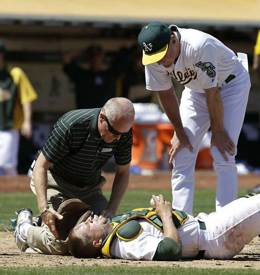 Oakland Athletics catcher Stephen Vogt receives attention from a trainer and manager Bob Melvin after colliding with Seattle Mariners' Dustin Ackley at home plate in the sixth inning of a baseball game Wednesday, Aug. 21, 2013, in Oakland, Calif. (AP Photo/Ben Margot) Photo: Ben Margot, Associated Press
