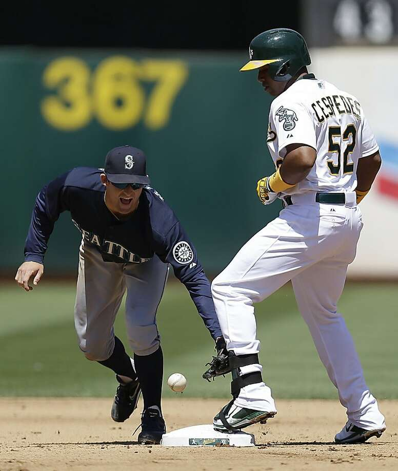 Seattle Mariners second baseman Brad Miller, left, drops the ball as Oakland Athletics' Yoenis Cespedes tags up with a double in the fourth inning of a baseball game on Wednesday, Aug. 21, 2013, in Oakland, Calif. (AP Photo/Ben Margot) Photo: Ben Margot, Associated Press