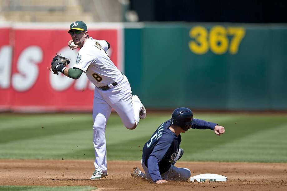 OAKLAND, CA - AUGUST 21: Brad Miller #5 of the Seattle Mariners breaks up a double play attempt by Jed Lowrie #8 of the Oakland Athletics during the third inning at O.co Coliseum on August 21, 2013 in Oakland, California. (Photo by Jason O. Watson/Getty Images) Photo: Jason O. Watson, Getty Images