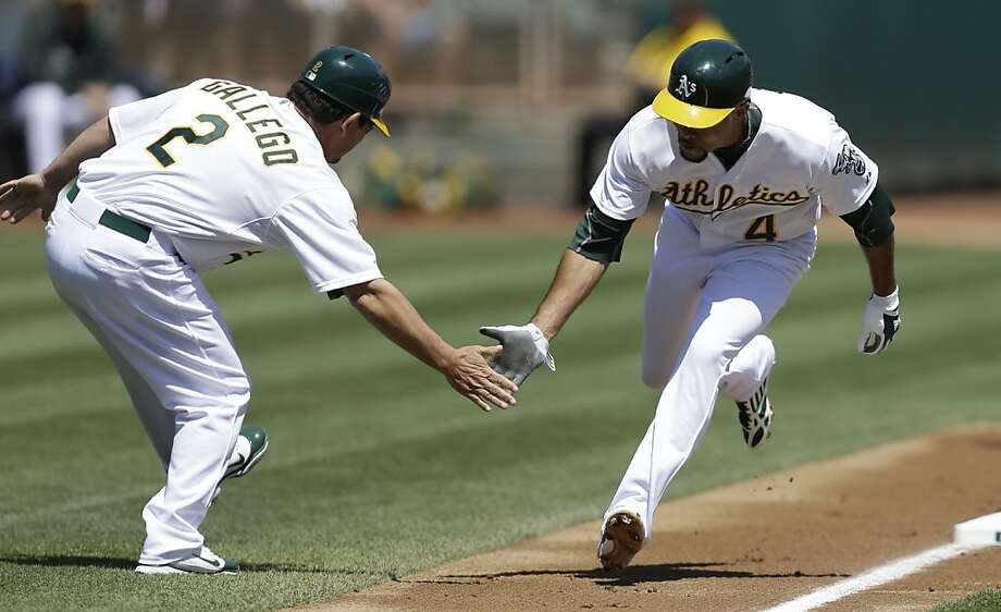 Oakland Athletics' Coco Crisp, right, is congratulated by third base coach Mike Gallego after hitting a home run off Seattle Mariners' Hisashi Iwakuma, of Japan, in the first inning of a baseball game on Wednesday, Aug. 21, 2013, in Oakland, Calif. (AP Photo/Ben Margot) Photo: Ben Margot, Associated Press