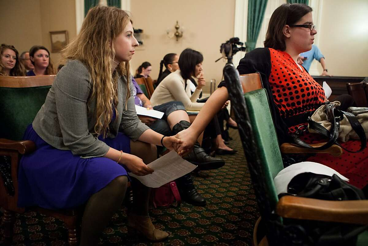 University of California, Berkeley students Sofie Karasek, left, and Aryle Butler, right, hold hands as they wait to testify about their experience with campus sexual assault before the Joint Legislative Audit Committee hearing at the State Capitol August 21, 2013 in Sacramento, California.