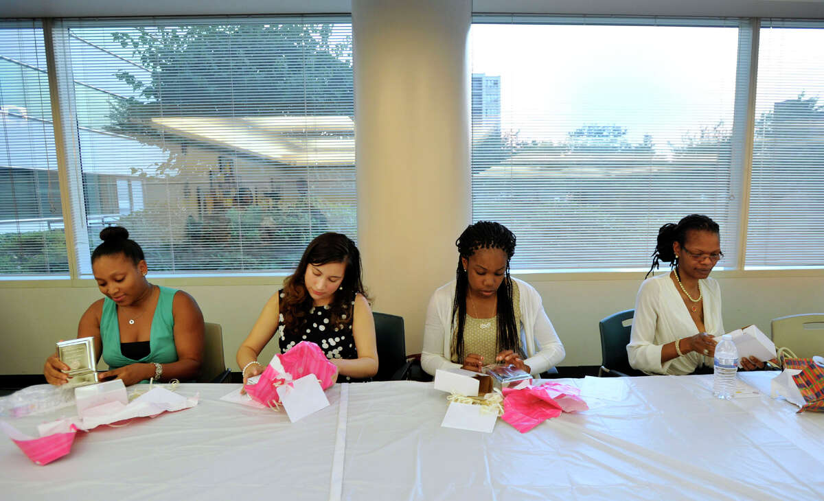 Scholarship winners from left, Shalimar Azima, Andrea Lopez Salazar, Ashyla Cody and Patrisha Williams open presents they were given at the NAACP first annual scholarship award ceremony at the Stamford Government Center on Wednesday, Aug. 21, 2013.