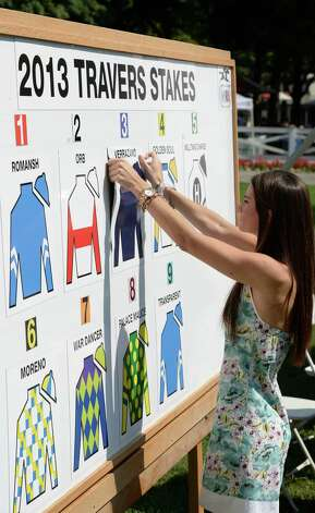 Teal Albertrani places the colors of Verrazano on the post position board in the paddock of the Saratoga Race Course Aug 21, 2013 in Saratoga Springs, N.Y. during the post position draw in which  Verrazano was named the morning line favorite to win the Travers Stakes.  The Travers runs on Saturday at Saratoga.  (Skip Dickstein/Times Union) Photo: SKIP DICKSTEIN
