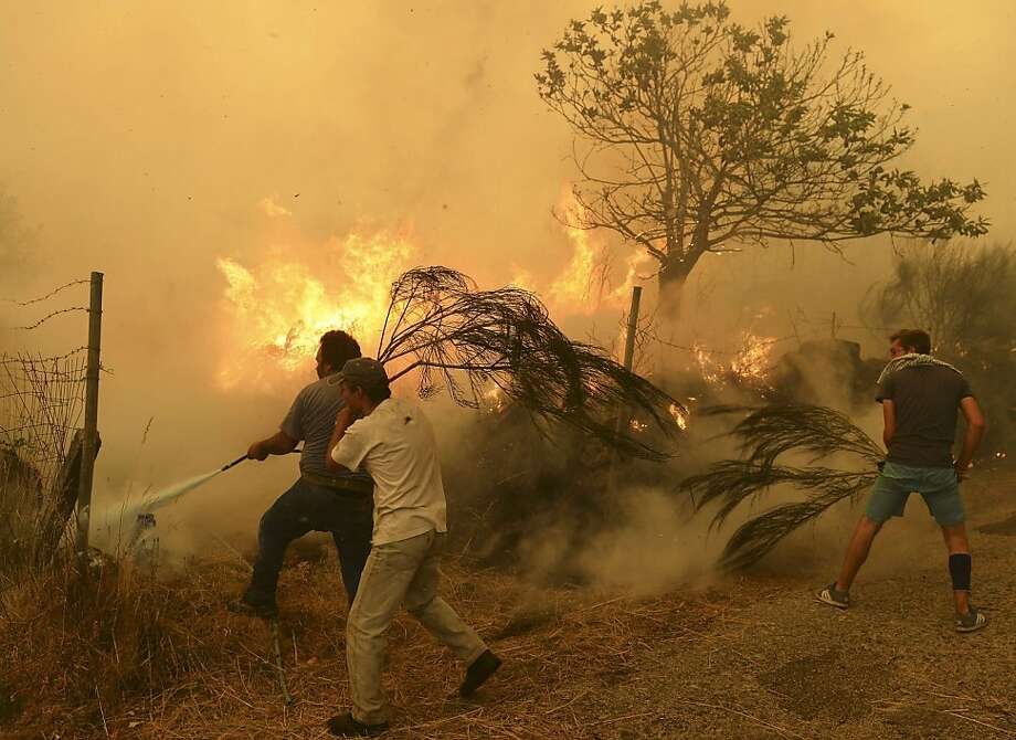 Wielding hoses and branches,residents battle a wildfire at Fornelo do Monte near 