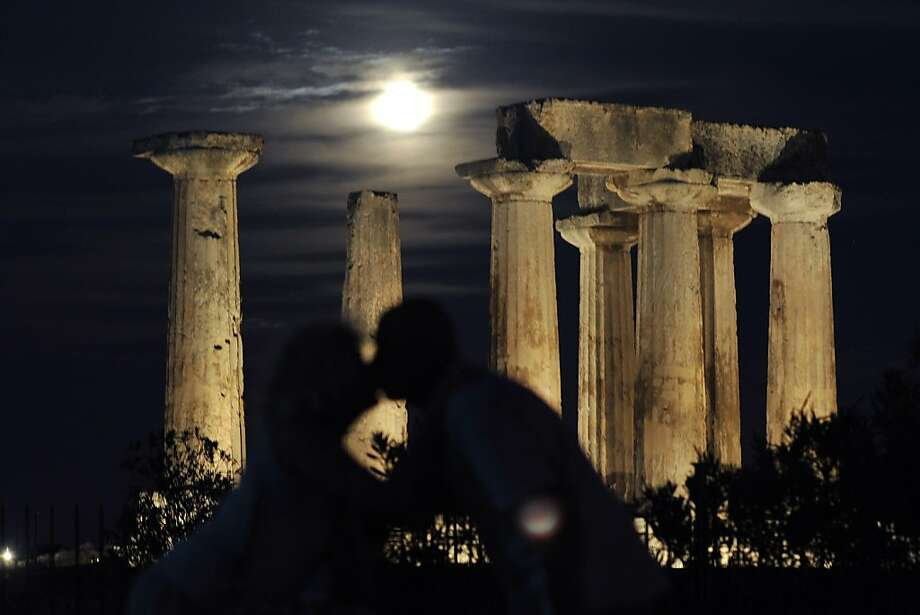 --EDITOR'S NOTE--CORRECTING BYLINE-- A couple kisses as the full moon rises behind the Temple of Apollo in Ancient Corinth on August 21, 2013. AFP PHOTO / VALERIE GACHEVALERIE GACHE/AFP/Getty Images Photo: Valerie Gache, AFP/Getty Images