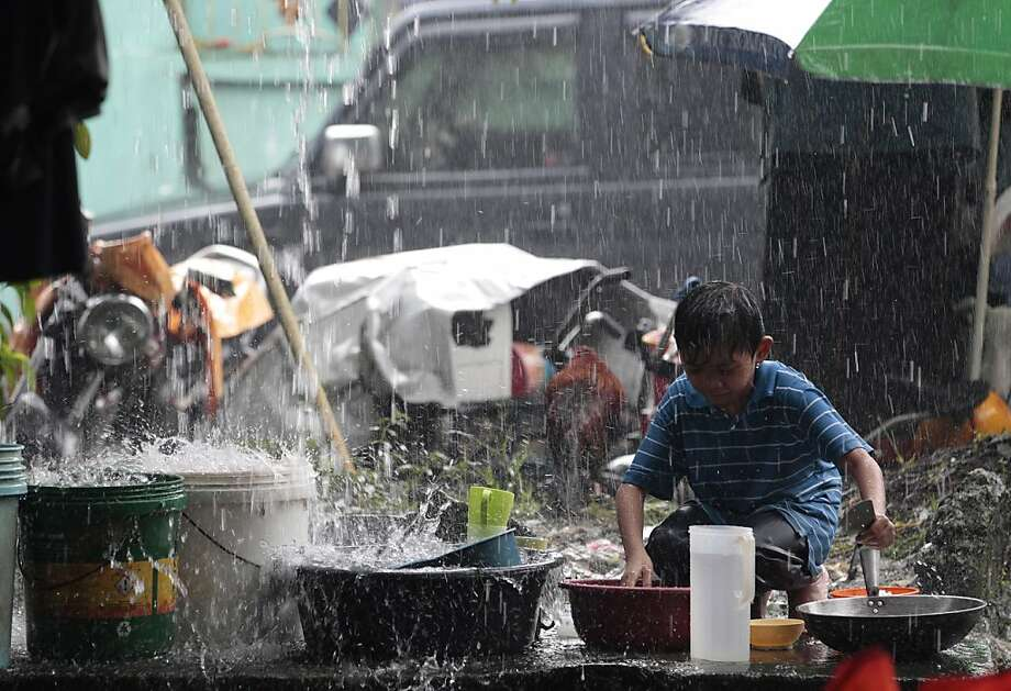 A Filipino boy cleans dishes at a temporary evacuation center as rain pours in suburban San Mateo, east of Manila, Philippines on Wednesday, Aug. 21, 2013. Earlier this week Tropical Storm Trami wreaked havoc in the country, causing eight deaths and severely flooding wide swaths of the capital Manila. Trami is bearing down on heavily populated northern Taiwan, prompting schools and offices to close.  (AP Photo/Aaron Favila) Photo: Aaron Favila, Associated Press