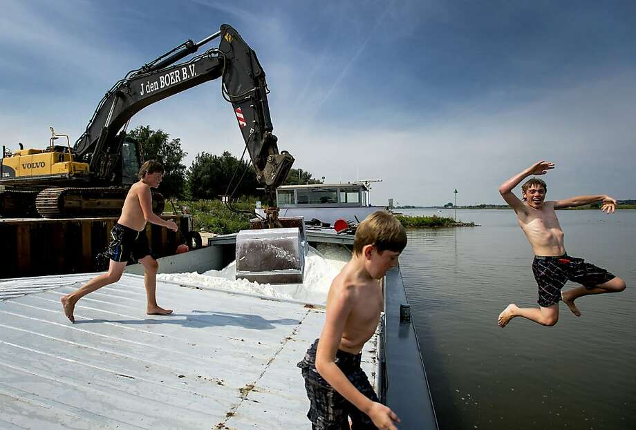 Children jump into water as a ship containing road salt is being unloaded at a dock in Lienden, central Netherlands, on August 21, 2013. AFP PHOTO/ANP/ ROBIN VAN LONKHUIJSEN  netherlands outROBIN VAN LONKHUIJSEN/AFP/Getty Images Photo: Robin Van Lonkhuijsen, AFP/Getty Images