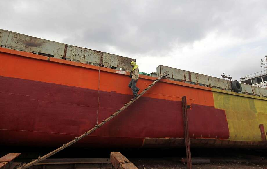 A Bangladeshi laborer walks down from a ferry being refurbished at a dockyard in Keraniganj, near Dhaka, Bangladesh, Wednesday, Aug. 21, 2013. Laborers engaged in building ferries, that involves welding, cutting and painting, earn less than US$ 4 a day. (AP Photo/A.M. Ahad) Photo: A.M. Ahad, Associated Press