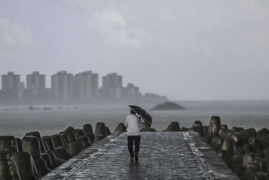 A man walks along the waterfront at Nariman Point in Mumbai, India, on Wednesday, Aug. 21, 2013. Volatility in India's rupee rose to a three-year high as the central bank's steps to support growth countered concern the U.S. will pare stimulus as early as next month. Photographer: Dhiraj Singh/Bloomberg Photo: Dhiraj Singh, Bloomberg