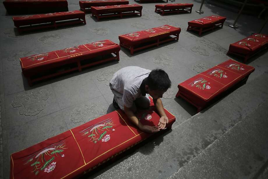 A man offers prayers to his deceased relatives on the Ghost Festival at Longhua Temple in Shanghai, China, Wednesday, Aug. 21, 2013. The festival is to worship ancestors in China. (AP Photo/Eugene Hoshiko) Photo: Eugene Hoshiko, Associated Press
