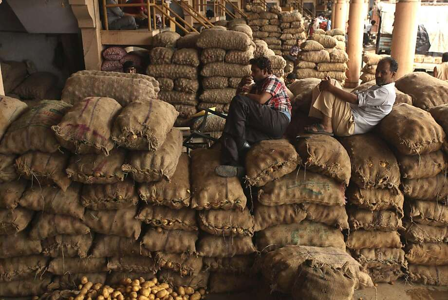 An Indian man drinks tea as he sits on sacks of potatoes at a wholesale market in Ahmadabad, India, Wednesday, Aug. 21, 2013. The Indian economy, Asia's third largest, grew 5 percent in the financial year ended March, its slowest in a decade and well off the 8 percent pace it had averaged over those 10 years. The Indian rupee has plumbed new lows against the dollar on a near daily basis, showing the pressure of a current account deficit that has swelled from high import costs.(AP Photo/Ajit Solanki) Photo: Ajit Solanki, Associated Press