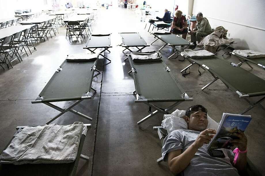 In this Tuesday, Aug. 20, 2013, Buck Meadows resident Victor Ojeda, who was evacuated due to the Rim Fire, lies on a cot and reads the Red Cross Shelter at the Mother Lode Fairgrounds in Sonora, Calif., where he spent the night. The remote blaze in Stanislaus National Forest west of Yosemite grew to more than 25 square miles Wednesday, and was only 5 percent contained, threatening homes, hotels and camp buildings.(AP Photo/The Modesto Bee, Andy Alfaro) LOCAL TV OUT (KXTV10, KCRA3, KOVR13, FOX40, KMAX31, KQCA58, CENTRAL VALLEY TV); LOCAL PRINT OUT (TURLOCK JOURNAL, CERES COURIER, OAKDALE LEADER, MODESTO VIEW, PATTERSON IRRIGATOR, MANTECA BULLETIN, RIPON, RECROD, SONORA UNION DEMOCRAT, AMADOR LEDGER DISPATCH, ESCALON TIMES, CALAVERAS ENTERPRISE, RIVERBANKS NEWS) LOCAL INTERNET OUT (TURLOCK CITY NEWS.COM, MOTHER LODE.COM) Photo: Andy Alfaro, Associated Press