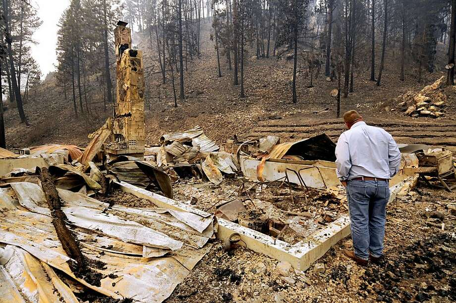 U.S. Sen. Jon Tester, D-Mont., looks at the remains of a Lolo Creek home that was destroyed by the West Fork II fire when it swept down the Lolo Creek canyon, Wednesday, Aug. 21, 2013 near Lolo, Mont. The fire burned four other homes as well along the U.S. Highway 12 corridor. (AP Photo/Missoulian, Kurt Wilson) Photo: Kurt Wilson, Associated Press