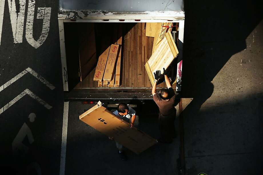 NEW YORK, NY - AUGUST 21:  Men load a truck as seen from the Manhattan Bridge on August 21, 2013 in New York City. The island of Manhattan is connected to the mainland by a series of historic bridges which thousands of New Yorkers use on a daily bases. Despite the changing landscape of New York, life under the bridges offers a glimpse of a city where the rhythms of life have changed little over the years. (Photo by Spencer Platt/Getty Images) Photo: Spencer Platt, Getty Images