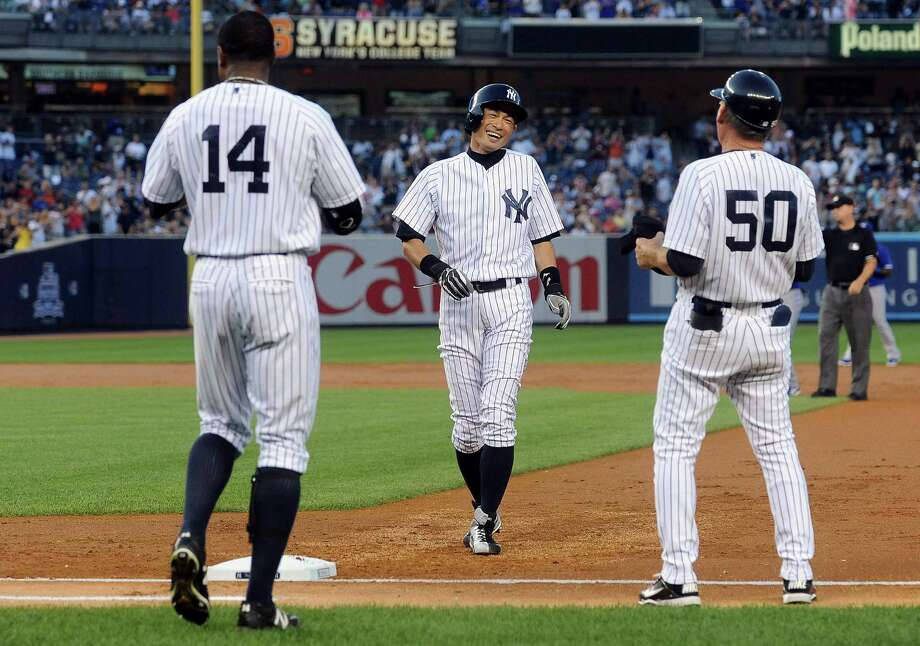 New York Yankees right fielder Ichiro Suzuki, center, on base after hitting his 4,000th career hit during an MLB game against the Toronto Blue Jays in New York, Aug. 21, 2013. With the hit, Suzuki joined a small club of players, which includes Ty Cobb and Pete Rose, who have had 4,000 hits during their career. (Barton Silverman/The New York Times) ORG XMIT: XNYT140 Photo: BARTON SILVERMAN / NYTNS
