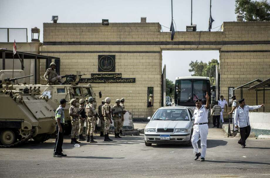 A police officer directs traffic outside of the gates of Torah prison, where former Egyptian President Hosni Mubarak has been held in Cairo. Photo: Bryan Denton / New York Times