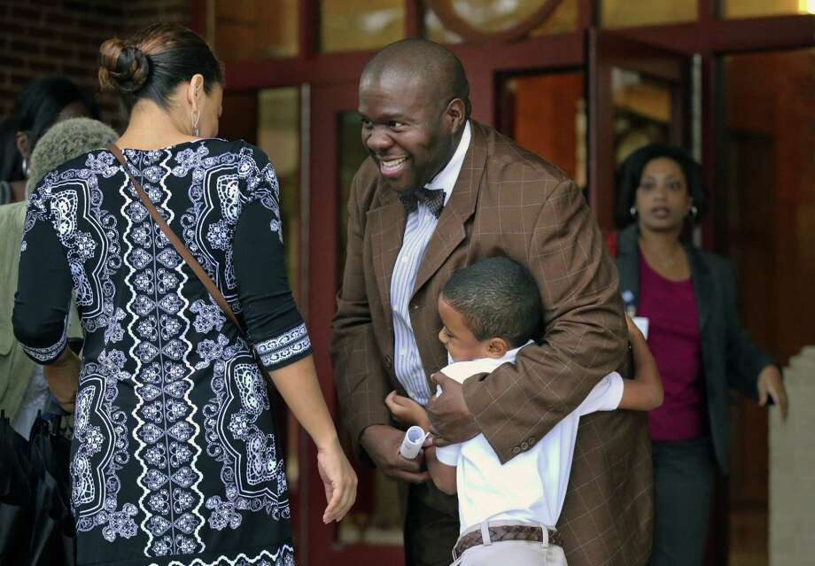 Ronald E. McNair Discovery Learning Academy media specialist Harold Grant welcomes children as they arrive at McNair High School on Wednesday, a day after an armed suspect caused an ordeal at their school in Decatur, Ga. Photo: John Spink / Associated Press