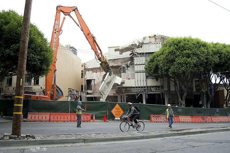 "The Pagoda Palace Theater, which has been an abandoned building in North Beach for 20 years, is demolished on August 20. Early Tuesday morning workers using a machine nicknamed ""The Muncher'' to bite off the iconic blade-shaped sign at the top of the structure. Work continues the rest of the week. Photo: SFMTA"