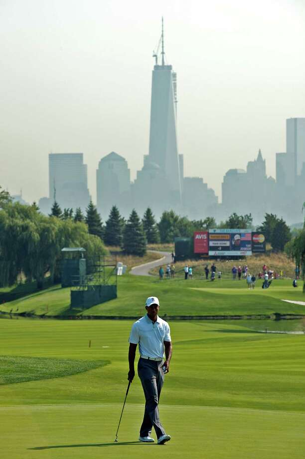 The skyline of lower Manhattan serves as the backdrop for Tiger Woods, who played only the front nine of Wednesday's pro-am for The Barclays in Jersey City, N.J., because of a stiff neck and back. Photo: Reena Rose Sibayan, MBR / The Jersey Journal