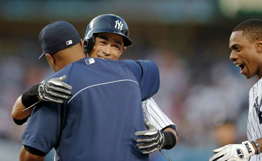 Vernon Wells, left, is among the Yankees congratulating Ichiro Suzuki on his 4,000th career hit. Photo: Kathy Willens, STF / AP