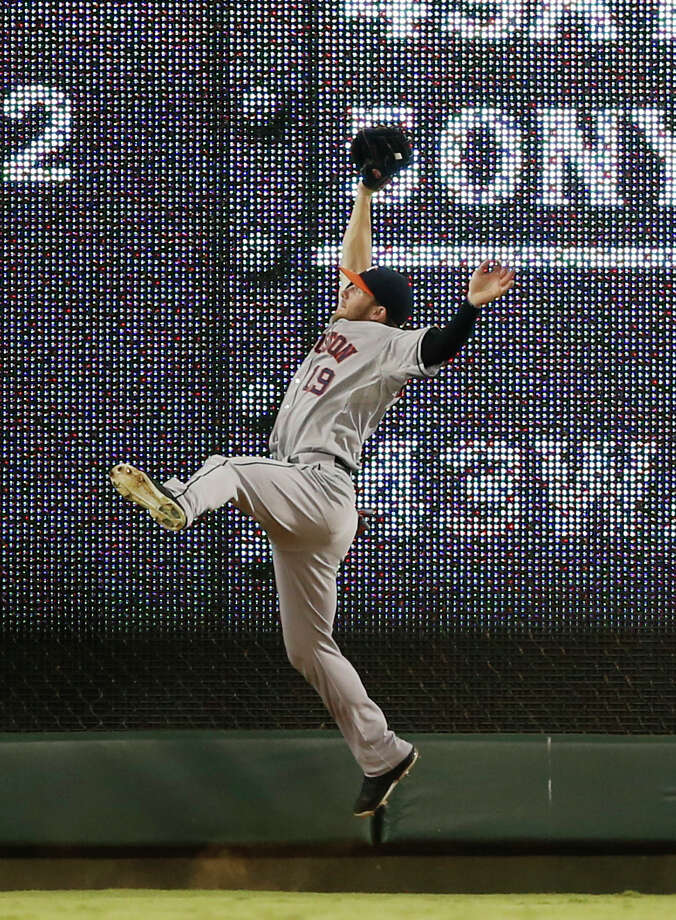 Astros left fielder Robbie Grossman takes a hit away from Rangers shortstop Elvis Andrus with an acrobatic catch in the fifth inning Wednesday night. Photo: Jim Cowsert, FRE / FR170531 AP