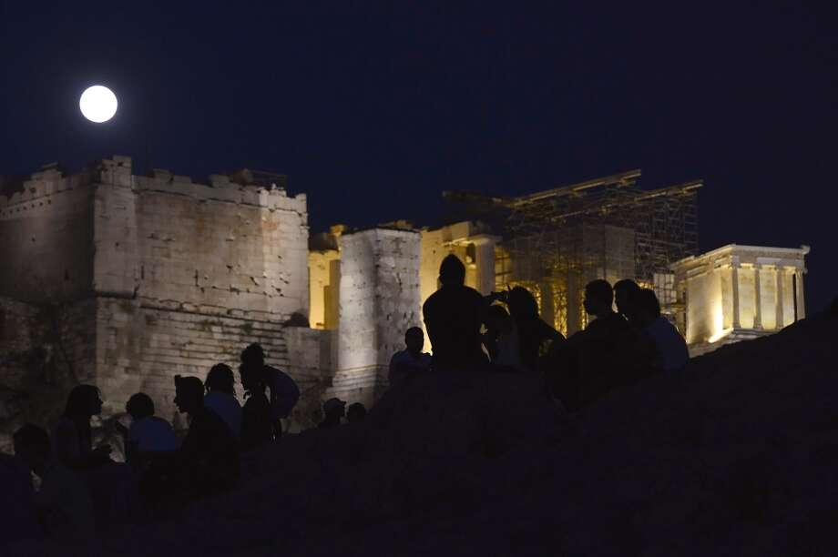Greeks and tourists watch the rising moon above the ancient Acropolis in Athens on August 20, 2013.  (LOUISA GOULIAMAKI/AFP/Getty Images) Photo: LOUISA GOULIAMAKI, AFP/Getty Images