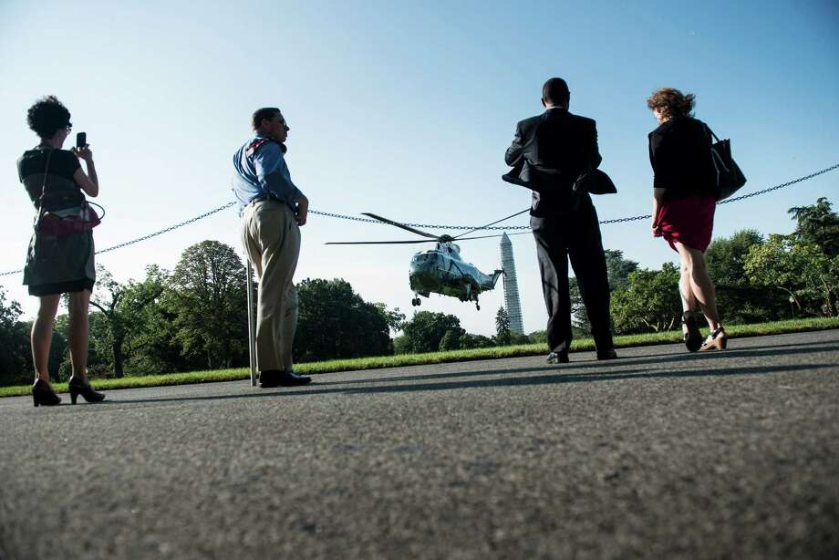 People watch as Marine One lands on the South Lawn at the White House August 22, 2013 in Washington, DC. Obama is traveling to New York to begin a two day bus tour of the state and Pennsylvania to promote his administration education policy. AFP PHOTO/Brendan SMIALOWSKIBRENDAN SMIALOWSKI/AFP/Getty Images ORG XMIT: 177621511 Photo: BRENDAN SMIALOWSKI, Getty / 2012 Brendan Smialowski