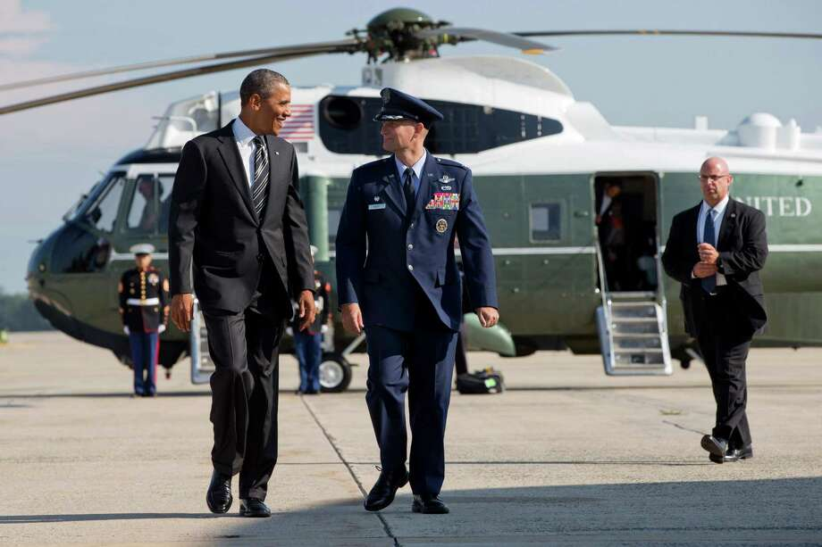 President Barack Obama walks with Col. William Knight, commander of the 11th Wing and Andrews Force Base, after getting off the Marine One helicopter and before boarding Air Force One, Thursday, Aug. 22, 2013, at Andrews Air Force Base, Md. The president was traveling to Buffalo, N.Y. to begin his two day bus tour where he is expected to speak about college financial aid. (AP Photo/Jacquelyn Martin) ORG XMIT: MDJM101 Photo: Jacquelyn Martin, AP / AP