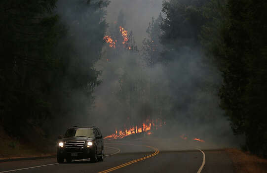 A car drives along US highway 120 as the Rim Fire burns out of control on August 21, 2013 in Buck Meadows, California. The Rim Fire continues to burn out of control and threatens 2,500 homes outside of Yosemite National Park. Over 400 firefighters are battling the blaze that is only 5 percent contained. Photo: Justin Sullivan, Getty Images / 2013 Getty Images
