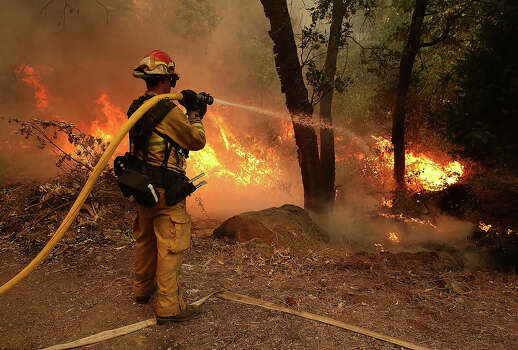 A firefighter from Ebbetts Pass Fire District uses a hose to cool down hot spots of  back fire as he battles the Rim Fire on August 21, 2013 in Groveland, California. The Rim Fire continues to burn out of control and threatens 2,500 homes outside of Yosemite National Park. Over 400 firefighters are battling the blaze that is only 5 percent contained. Photo: Justin Sullivan, Getty Images / 2013 Getty Images