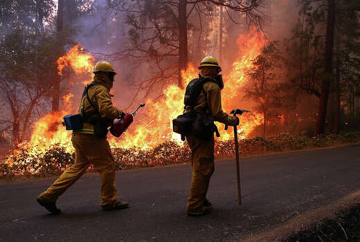 Firefighters from Ebbetts Pass Fire District monitor a back fire as they  battle the Rim Fire on August 21, 2013 in Groveland, California. The Rim Fire continues to burn out of control and threatens 2,500 homes outside of Yosemite National Park. Over 400 firefighters are battling the blaze that is only 5 percent contained. Photo: Justin Sullivan, Getty Images / 2013 Getty Images
