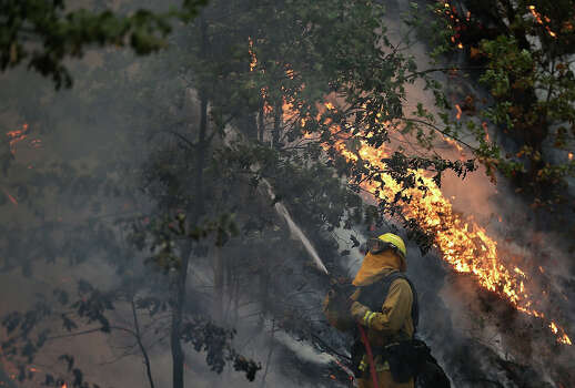 A firefighter from Ebbetts Pass Fire District uses a hose to cool down hot spots of  back fire while battling the Rim Fire on August 21, 2013 in Groveland, California. The Rim Fire continues to burn out of control and threatens 2,500 homes outside of Yosemite National Park. Over 400 firefighters are battling the blaze that is only 5 percent contained. Photo: Justin Sullivan, Getty Images / 2013 Getty Images