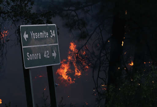 Flames from the Rim Fire burn near a road sign pointing towards Yosemite on August 21, 2013 in Groveland, California. The Rim Fire continues to burn out of control and threatens 2,500 homes outside of Yosemite National Park. Over 400 firefighters are battling the blaze that is only 5 percent contained. Photo: Justin Sullivan, Getty Images / 2013 Getty Images