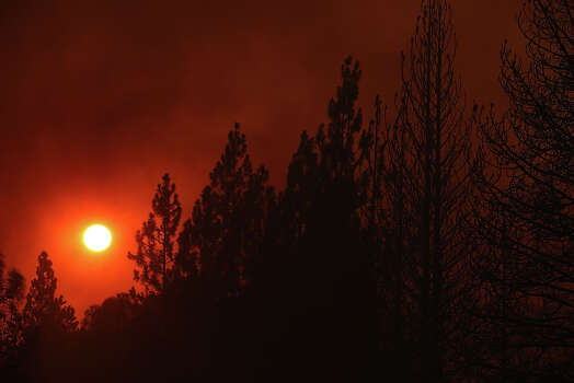The sun sets through heavy smoke from the Rim Fire on August 21, 2013 in Groveland, California. The Rim Fire continues to burn out of control and threatens 2,500 homes outside of Yosemite National Park. Over 400 firefighters are battling the blaze that is only 5 percent contained. Photo: Justin Sullivan, Getty Images / 2013 Getty Images