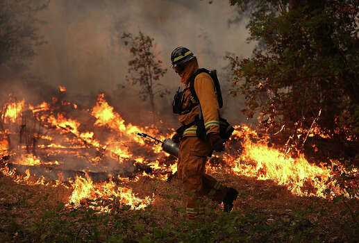 A firefighter from Ebbetts Pass Fire District uses a drip torch to light a back fire while battling the Rim Fire on August 21, 2013 in Groveland, California. The Rim Fire continues to burn out of control and threatens 2,500 homes outside of Yosemite National Park. Over 400 firefighters are battling the blaze that is only 5 percent contained. Photo: Justin Sullivan, Getty Images / 2013 Getty Images