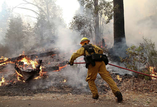 A firefighter from Ebbetts Pass Fire District uses a hose to cool down hot spots while battling the Rim Fire on August 21, 2013 in Groveland, California. The Rim Fire continues to burn out of control and threatens 2,500 homes outside of Yosemite National Park. Over 400 firefighters are battling the blaze that is only 5 percent contained. Photo: Justin Sullivan, Getty Images / 2013 Getty Images