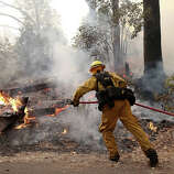 A firefighter from Ebbetts Pass Fire District uses a hose to cool down hot spots while battling the Rim Fire on August 21, 2013 in Groveland, California. The Rim Fire continues to burn out of control and threatens 2,500 homes outside of Yosemite National Park. Over 400 firefighters are battling the blaze that is only 5 percent contained.
