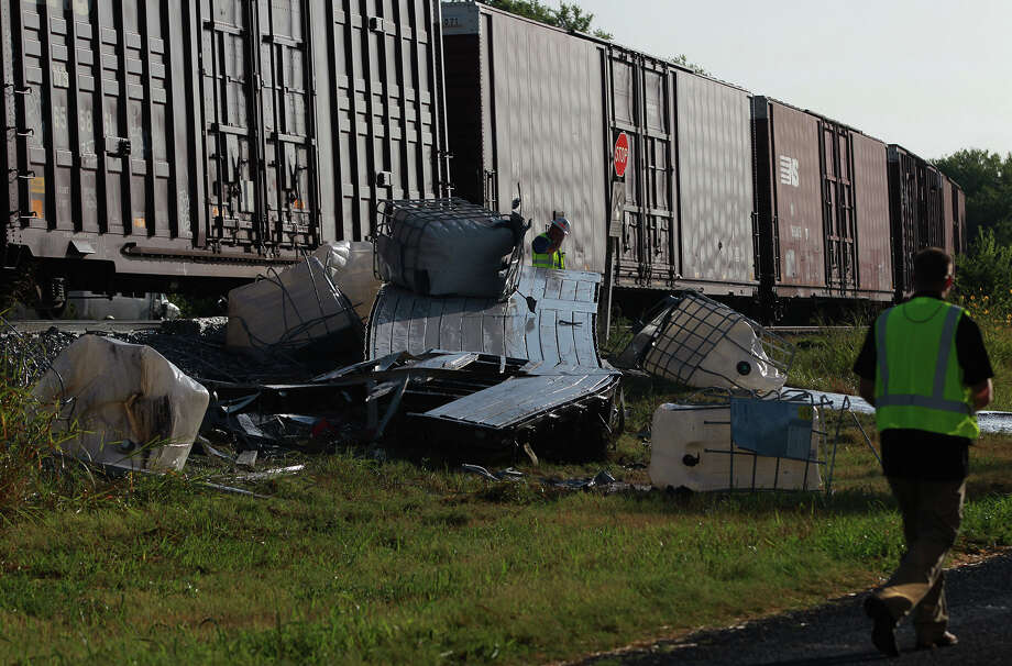 Remnants of an 18-wheeler tractor trailer rig are strewn on the side of the Union Pacific railway right of way in Von Ormy, Texas Thursday August 22, 2013 after it was hit by a freight train. Firefighters at the scene with Emergency Service District 5 said the truck was carrying a lubricating substance used for the gas or petroleum drilling industry and that the driver of the rig was not injured. Crews are currently working to remove the truck and get the southbound train on its way. Photo: JOHN DAVENPORT, SAN ANTONIO EXPRESS-NEWS / ©San Antonio Express-News/Photo may be sold to the public