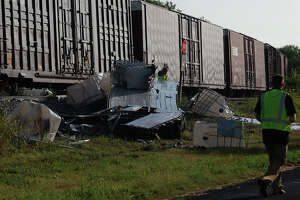 Remnants of an 18-wheeler tractor trailer rig are strewn on the side of the Union Pacific railway right of way in Von Ormy, Texas Thursday August 22, 2013 after it was hit by a freight train. Firefighters at the scene with Emergency Service District 5 said the truck was carrying a lubricating substance used for the gas or petroleum drilling industry and that the driver of the rig was not injured. Crews are currently working to remove the truck and get the southbound train on its way.